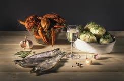 Alimento, casa da arte Ainda vida com os peixes secos das lagostas, a vodca e as batatas fervidas imagens de stock royalty free