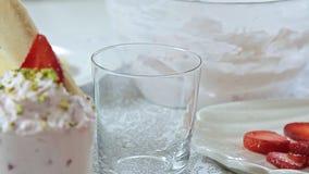 Alimento che disegna la crema del formaggio con la fragola ed i pistacchi video d archivio