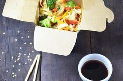 Alimento chinês, macarronetes com carne de porco e vegetais na caixa para viagem na tabela de madeira fotografia de stock royalty free