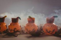 Alimento in contenitori della lanterna della presa o con le foglie di autunno durante il Halloween Immagini Stock