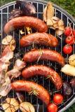 Alimento cotto Salsicce, bacon e verdure di maiale arrostite sul piatto della griglia, vista superiore, all'aperto immagini stock