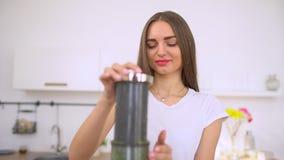 Alimento cru do suco vegetal - mulher comendo saudável com aipo juicing do juicer, os vegetais verdes e os frutos da maçã e filme