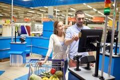 Alimento d'acquisto delle coppie al registratore di cassa della drogheria Fotografie Stock Libere da Diritti