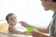 Alimento d'alimentazione del bambino del padre Fotografia Stock