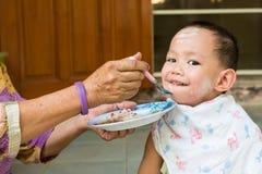 Alimento d'alimentazione della nonna al neonato tailandese Fotografie Stock Libere da Diritti