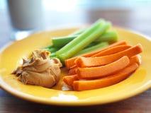 Alimento das crianças - manteiga de amendoim com aipo e cenouras. Imagens de Stock