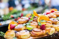 Alimento de abastecimento do bufete exterior Uvas das laranjas das bagas dos frutos frescos dos bolos e decorações coloridas da e Fotos de Stock Royalty Free