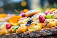 Alimento de abastecimento do bufete exterior Uvas das laranjas das bagas dos frutos frescos dos bolos e decorações coloridas da e Foto de Stock