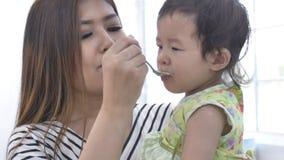 Alimento de alimentação da mãe asiática para sua filha em casa com cara do sorriso, conceito de família asiático feliz filme