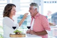 Alimento de alimentação da mulher ao homem fotos de stock