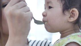 Alimento de alimenta??o da m?e asi?tica para sua filha em casa com cara do sorriso, conceito de fam?lia asi?tico feliz vídeos de arquivo