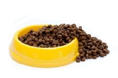 Alimento de animal doméstico en tazón de fuente amarillo Fotos de archivo