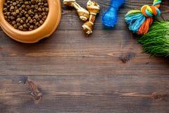 Alimento de cão de estimação seco na bacia na zombaria de madeira da opinião superior do fundo acima imagem de stock