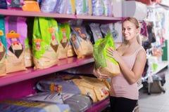 Alimento de compra do cliente da mulher para animais de estimação na loja Imagens de Stock Royalty Free