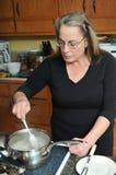 Alimento de mistura da mulher na cozinha fotos de stock