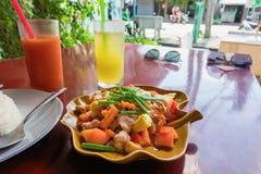 Alimento de Tail?ndia, carne de porco fritada picante doce com os vegetais com arroz cru imagens de stock