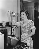 Alimento dell'assaggio della donna che cucina sulla stufa Immagini Stock