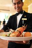 Alimento della holding del cameriere del ristorante Immagine Stock