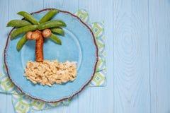 Alimento di divertimento per i bambini - piselli e palma della salsiccia su un'isola rimescolata delle uova Fotografie Stock Libere da Diritti