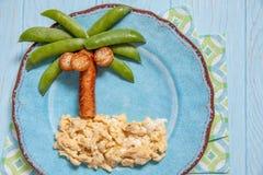 Alimento di divertimento per i bambini - piselli e palma della salsiccia su un'isola rimescolata delle uova Fotografie Stock