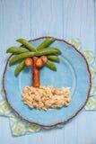 Alimento di divertimento per i bambini - piselli e palma della salsiccia su un'isola rimescolata delle uova Immagine Stock Libera da Diritti
