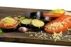 Alimento di estate: melanzana e pomodoro affettati Pomodori, melanzane, formaggi, aglio e sedano su un bordo di legno Fotografia Stock