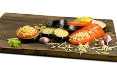 Alimento di estate: melanzana e pomodoro affettati Pomodori, melanzane, formaggi, aglio e sedano su un bordo di legno Immagine Stock