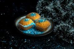 Alimento di Natale - i muffin del limone spruzzati con blu e bianco spruzza sul fondo di Natale immagine stock