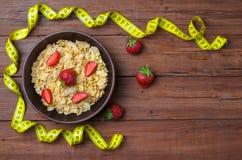 Alimento dietético: flocos e morangos de milho em um tampo da mesa de madeira imagens de stock