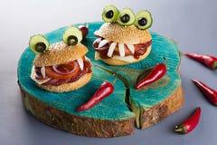 Alimento do partido de Dia das Bruxas Os Hamburger do monstro fecham-se acima com pimentas de pimentão vermelho foto de stock