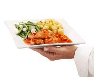 Alimento do serviço do cozinheiro chefe em uma placa Imagens de Stock