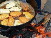 Alimento doce ecuadorian tradicional - o queijo Empanadas cozinhou no fogo aberto no potenciômetro grande com óleo foto de stock royalty free