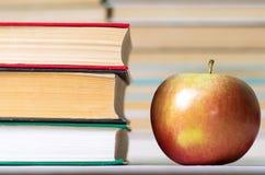 Alimento e conoscenza di una mela ed accanto ad una pila di libri dalla copertina rigida Fotografia Stock