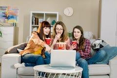 Alimento e film Tre sorelle graziose emozionali che mangiano popcorn quando l'attimo di sorveglianza di programma di sport o di f immagine stock