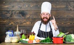Alimento e vegetariano in buona salute Uomo felice che cucina nella cucina Cuoco unico professionista in uniforme del cuoco Essen fotografia stock