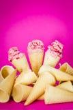 Alimento, gelado de morango em cones do waffle no fundo cor-de-rosa, papel de parede vertical Foto de Stock Royalty Free