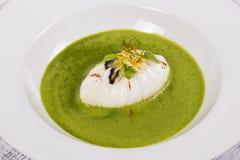 Alimento gourmet - ovo escalfado e sopa saudável verde com flores e folhas do verde Imagens de Stock