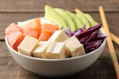 alimento hawaiano della ciotola del colpo piatto con riso, il salmone, l'avocado, il cavolo ed il formaggio, su una tavola di leg immagine stock libera da diritti