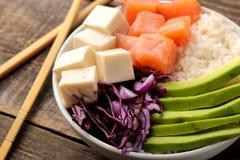 alimento hawaiano della ciotola del colpo piatto con riso, il salmone, l'avocado, il cavolo ed il formaggio, su una tavola di leg immagini stock