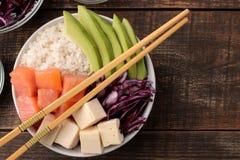 alimento hawaiano della ciotola del colpo piatto di riso, del salmone, dell'avocado, del cavolo e del formaggio, su una tavola di fotografia stock libera da diritti