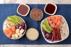 alimento hawaiano della ciotola del colpo un piatto con riso, il salmone, l'avocado, il cavolo ed il formaggio accanto ad una mof fotografia stock