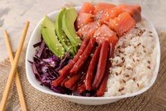 alimento hawaiano della ciotola del colpo un piatto con riso, il salmone, l'avocado, il cavolo ed il formaggio su un fondo legger fotografia stock