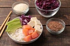 alimento hawaiano della ciotola del colpo un piatto con riso, il salmone, l'avocado, il cavolo ed il formaggio, vicino a sesamo S fotografia stock