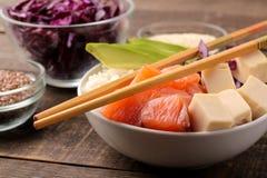 alimento hawaiano della ciotola del colpo un piatto con riso, il salmone, l'avocado, il cavolo ed il formaggio, vicino a sesamo S immagine stock