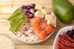 alimento hawaiano della ciotola del colpo un piatto di riso, del salmone, dell'avocado, del cavolo e del formaggio accanto ai sem immagine stock libera da diritti