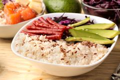 alimento hawaiano della ciotola del colpo un piatto di riso, del salmone, dell'avocado, del cavolo e del formaggio accanto ai sem fotografia stock