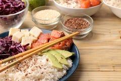 alimento hawaiano della ciotola del colpo un piatto di riso, del salmone, dell'avocado, del cavolo e del formaggio accanto ai sem immagini stock