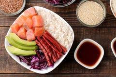 alimento hawaiano della ciotola del colpo un piatto di riso, del salmone, dell'avocado, del cavolo e del formaggio, accanto alla  immagini stock