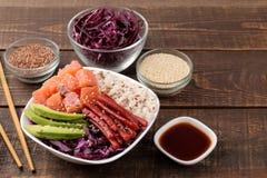 alimento hawaiano della ciotola del colpo un piatto di riso, del salmone, dell'avocado, del cavolo e del formaggio, accanto alla  fotografia stock