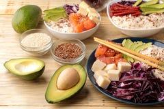 alimento hawaiano della ciotola del colpo un piatto di riso, del salmone, dell'avocado, del cavolo e del formaggio accanto a sesa immagine stock